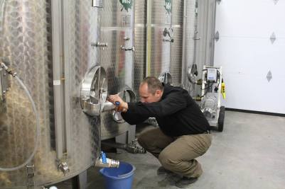 Greg Melien, owner operator of Boreal Winery, inspecting his vats.